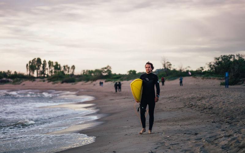 Full length of man walking on beach against sky