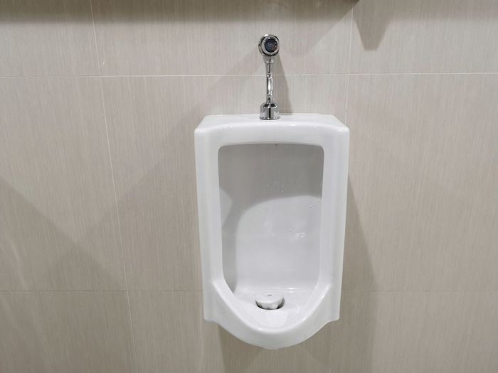 Close-Up Of Urinal In Bathroom