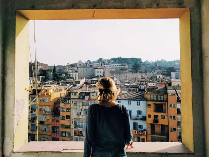 Rear View Of Young Woman Standing Against Cityscape