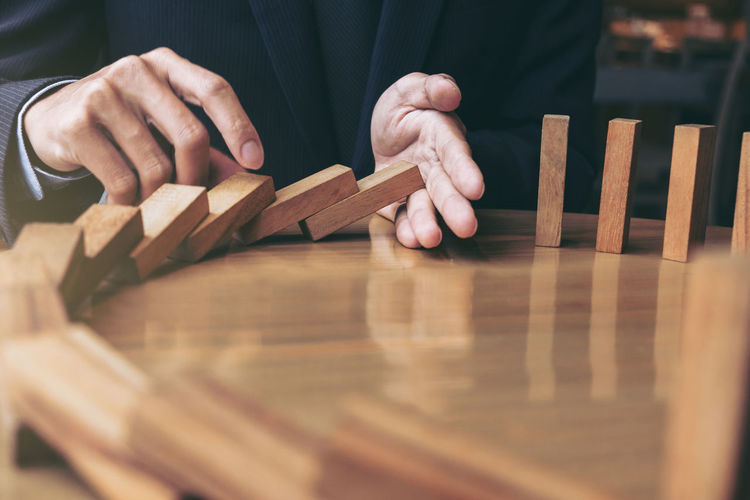 Entrepreneur Businessman Close-up Day Finance Holding Human Body Part Human Hand Indoors  Investment Marketing Men Midsection One Person People Planner Prevention Protection Stop Strategy Table Wood - Material Wood Game Wooden Wooden Block