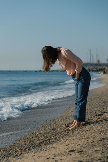 Side view of woman on beach against clear sky