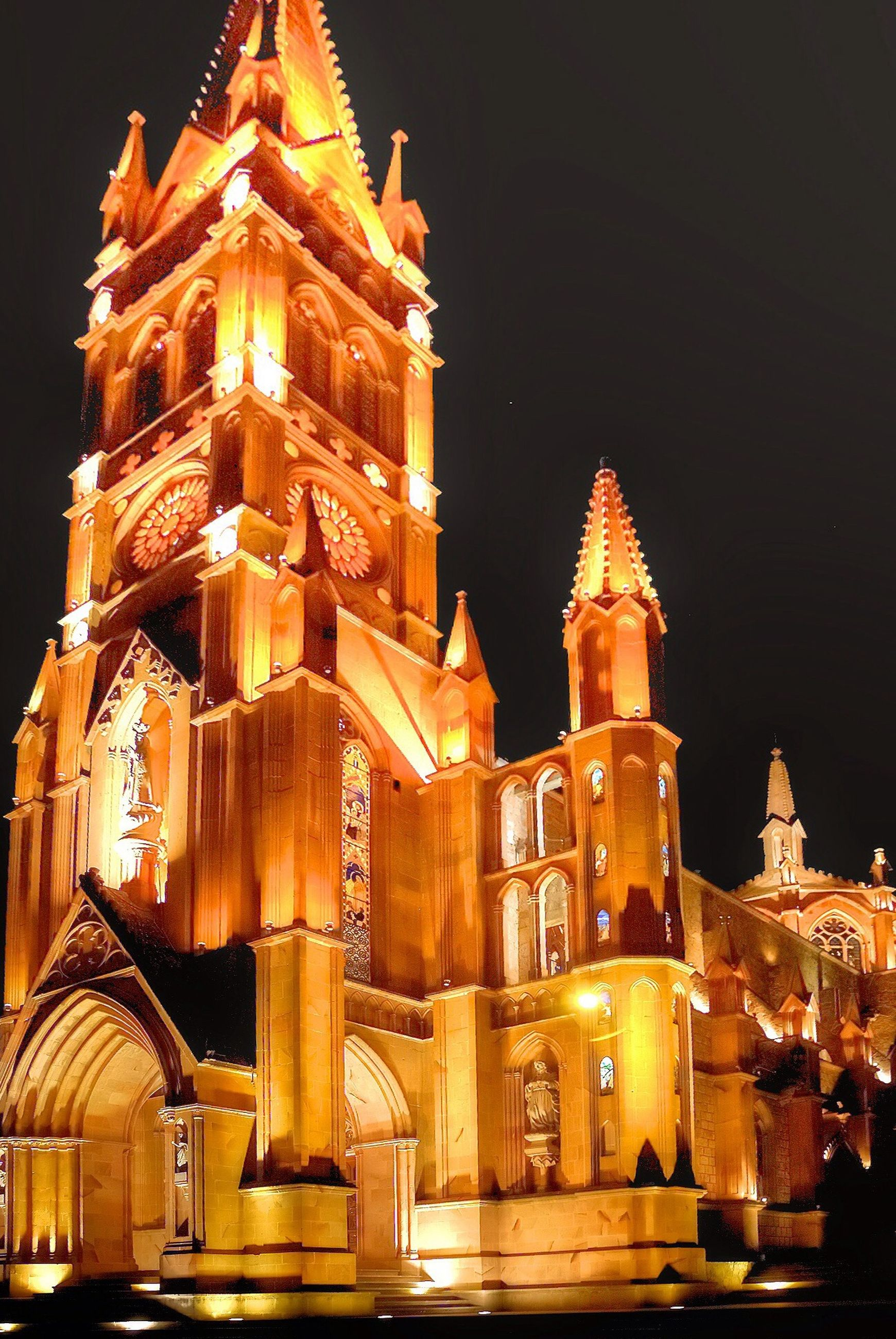 illuminated, night, religion, place of worship, spirituality, building exterior, architecture, built structure, church, temple - building, low angle view, lighting equipment, history, outdoors, sky, no people, glowing, light - natural phenomenon
