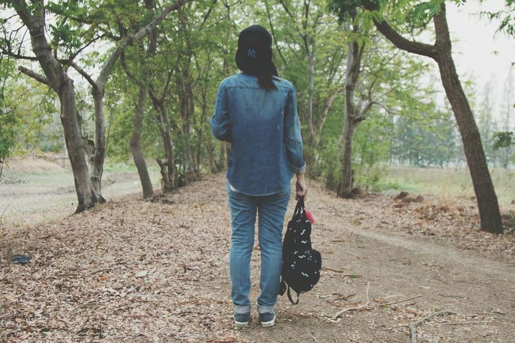 Rear View Of Woman Holding Backpack And Standing On Messy Field