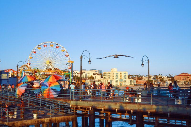 People Walking At Santa Monica Pier Against Clear Sky