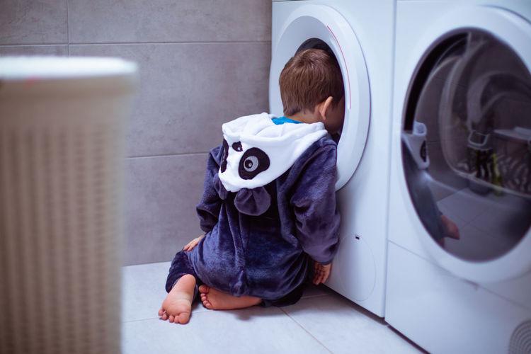 Rear view of boy peeking in washing machine