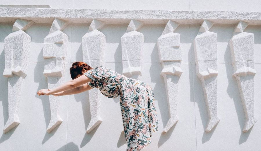 Side view of woman bending by white wall during sunny day