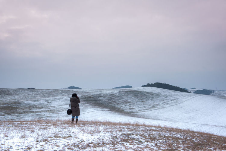 Rear view of man walking on shore during winter