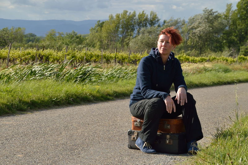 Full length of woman sitting on suitcases over road