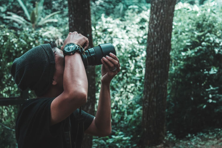 Man Photographing Through Camera At Forest