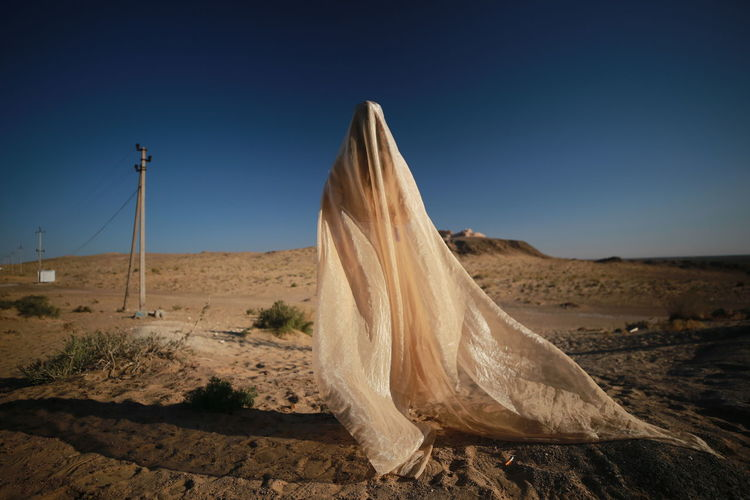 Person covered in textile standing on land