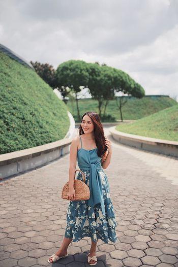 Full length of woman standing in park against sky