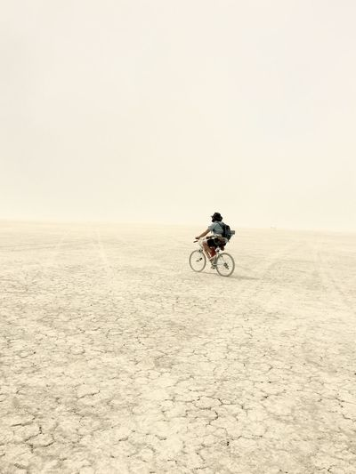 Full length of man riding bicycle at desert
