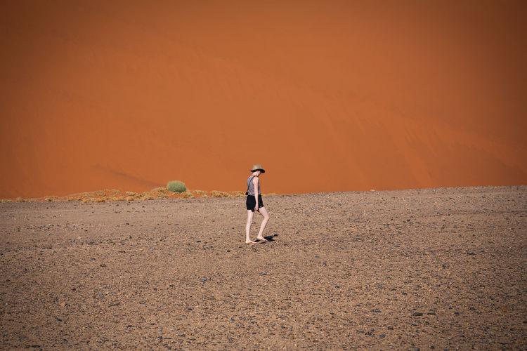 Full length of woman walking in desert on sunny day