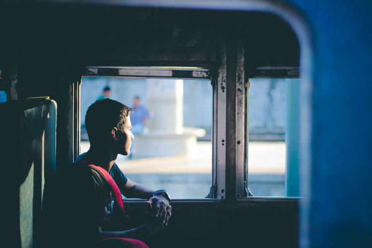 Side View Of Thoughtful Man Looking Through Window In Train