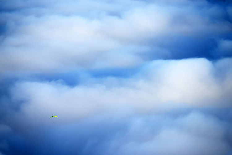 Person paragliding against clouds over el teide national park