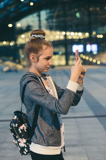 Woman photographing on smart phone while standing in airport