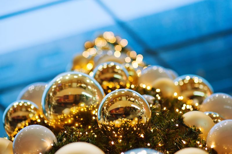 festive Christmas decorations Celebration Christmas Decoration Holiday Christmas Decoration Close-up Shiny christmas tree Selective Focus Luxury Christmas Lights Glass - Material Sphere Christmas Ornament Reflection Event No People Illuminated Indoors