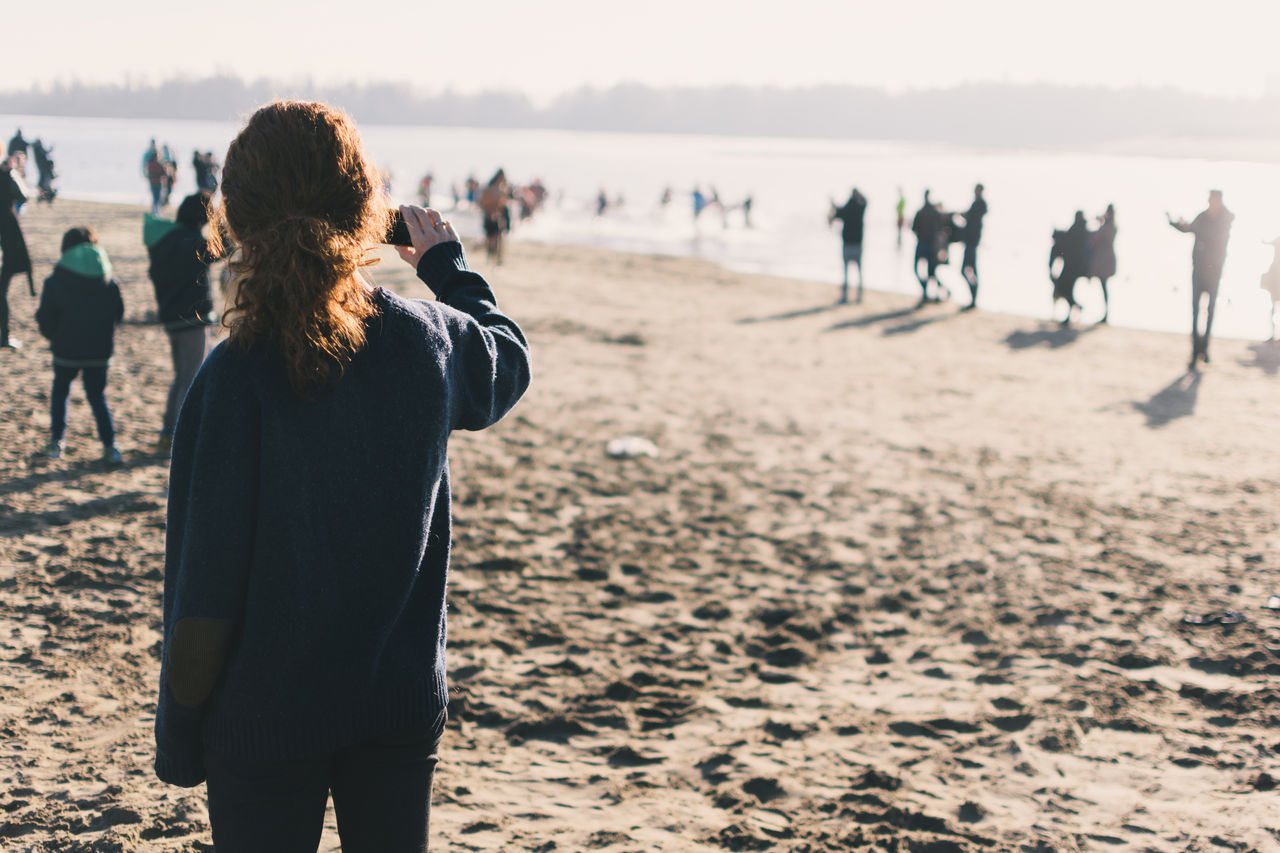 Rear view of woman photographing through mobile phone while standing at beach