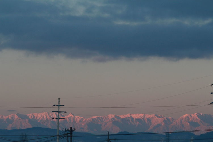 Scenic View Of Mountain Range Against Cloudy Sky During Sunrise