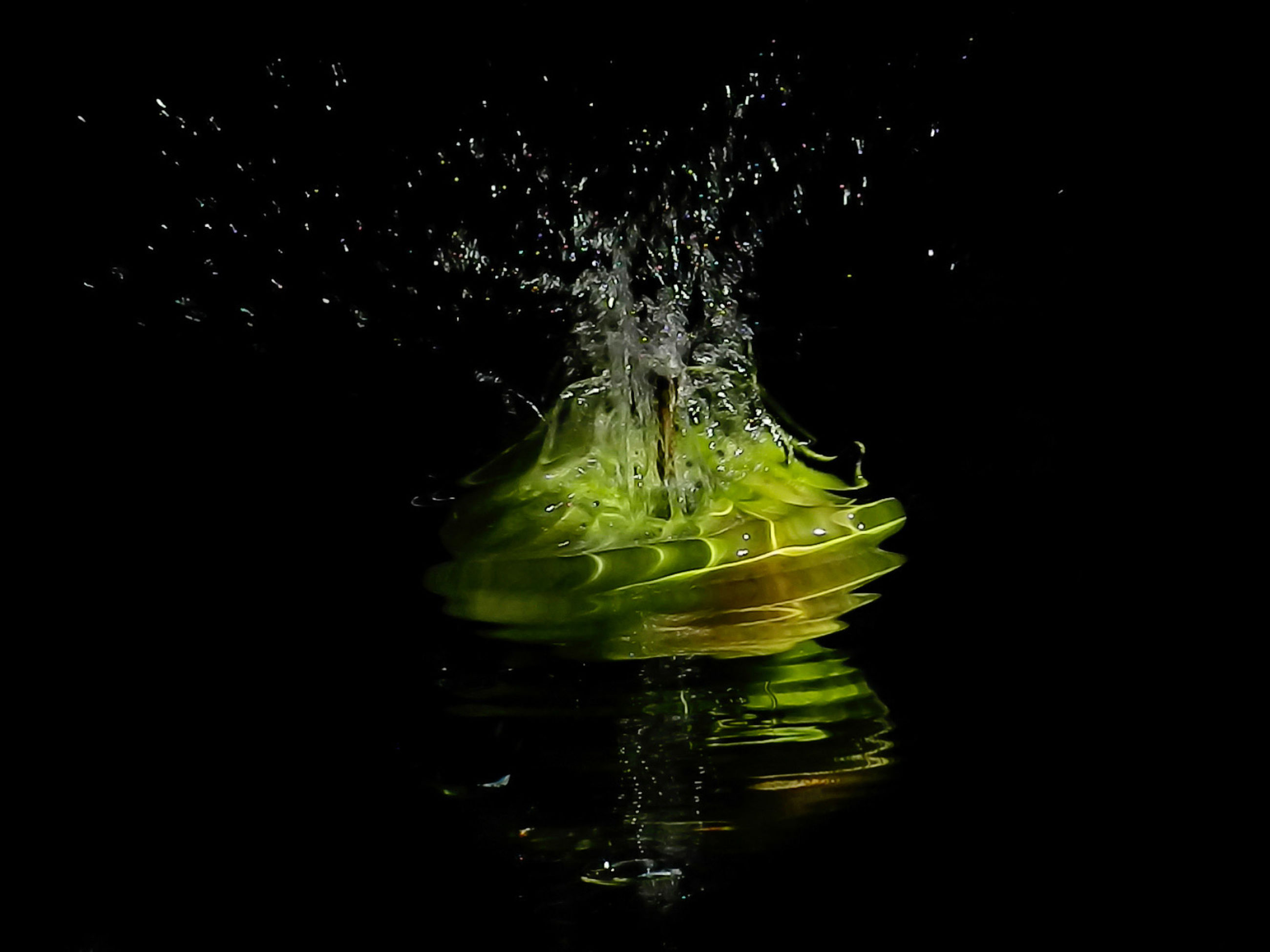 black background, splashing, studio shot, motion, water, food and drink, freshness, indoors, yellow, green, impact, darkness, no people, food, night, healthy eating, drop, refreshment, nature, wellbeing, reflection, light, drink, close-up, falling, macro photography, copy space, leaf
