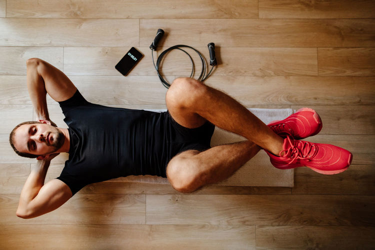 Midsection of man lying down on hardwood floor
