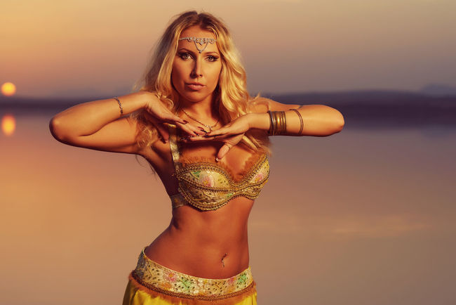 Beautiful blonde belly dancer woman on a lake in the evening. Golden colors Belly Dance Blonde Dancing Moving Nature Standing Woman Art Attractive Beautiful Woman Beauty In Nature Belly Dancer Belly Dancing Caucasian Costume Golden Color Lake Landscape One Person Outdoors Pose Sunset Water Young Adult Young Women