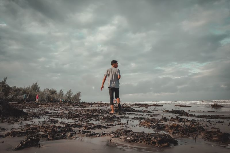 Rear view of man walking at beach against cloudy sky