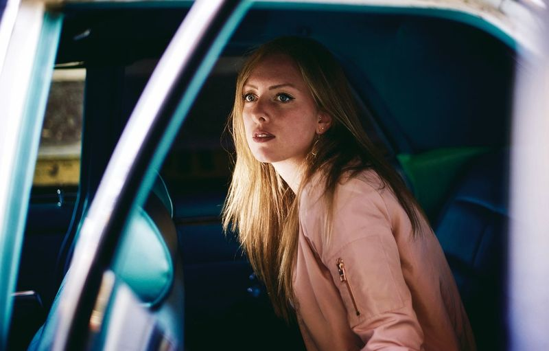 Side view of beautiful young woman sitting in car seen through window