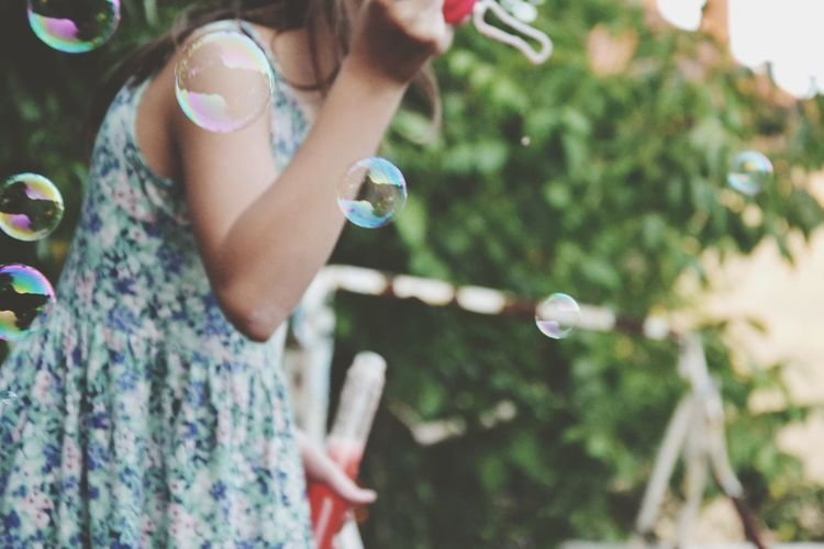 Midsection of woman blowing bubbles