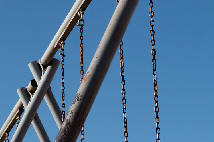 Low Angle View Of Swing At Playground Against Clear Blue Sky