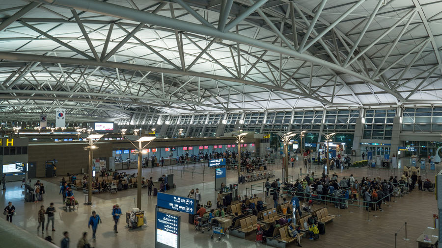 SEOUL, SOUTH KOREA - OCTOBER 22, 2015: Big hall with people in waiting areas. Incheon International Airport is the primary one serving the Seoul Capital Area, and it is of the largest and busiest airports in the world Airport Architecture ASIA Busy Crowd Departure Hall Horizontal Incheon Indoors  Lounge People Seoul South Korea Terminal Tourism Traffic Travel Traveler Wait Waiting Room