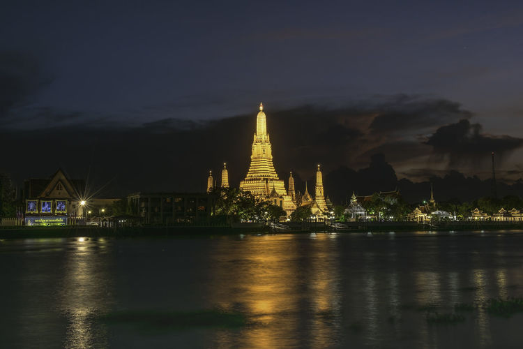Wat Arun or Wat Arun is a temple on the west bank of the Chao Phraya River, Bangkok, Thailand. Architecture Belief Building Building Exterior Built Structure Illuminated Nature Night No People Outdoors Place Of Worship Reflection Religion River Sky Spirituality Travel Destinations Water Waterfront