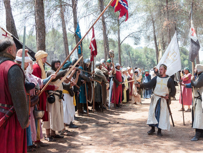 Tiberias, Israel, July 01, 2017 : Participants in the reconstruction of Horns of Hattin battle in 1187 in the role of King of Jerusalem makes a speech before the soldiers in the camp before the campaign near TIberias, Israel 1187 Battle Cross Crusaders Day Field Guy De Lusignan Hattin Heat Heritage History Horn Israel Jerusalem KINGDOM Muslims Outdoors Palestine People Reconstruction Religion Saladin Templars War Weapons