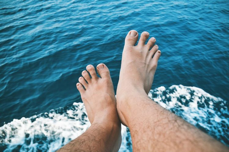 Low section of person legs by sea
