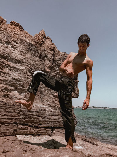 Full length of shirtless man on rock at beach against clear sky