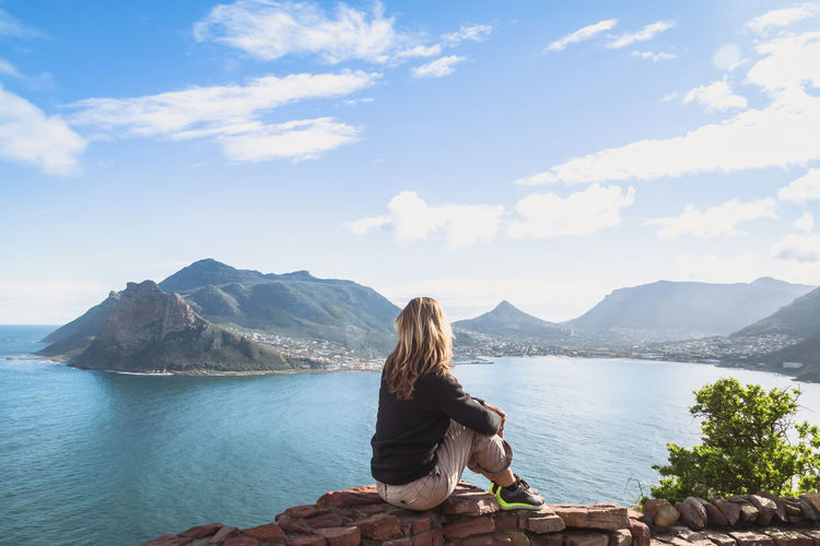 Side view of woman sitting on stone retaining wall while looking at hout bay against sky