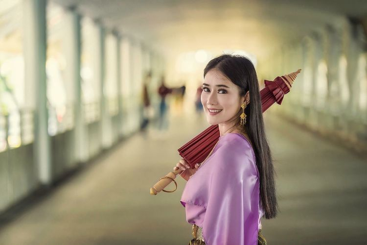 Portrait Of Smiling Woman Holding Traditional Umbrella While Standing In Corridor