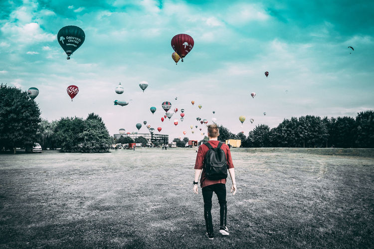 Rear view of people with balloons flying against sky