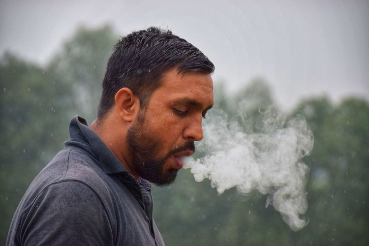 Side view of man smoking against trees