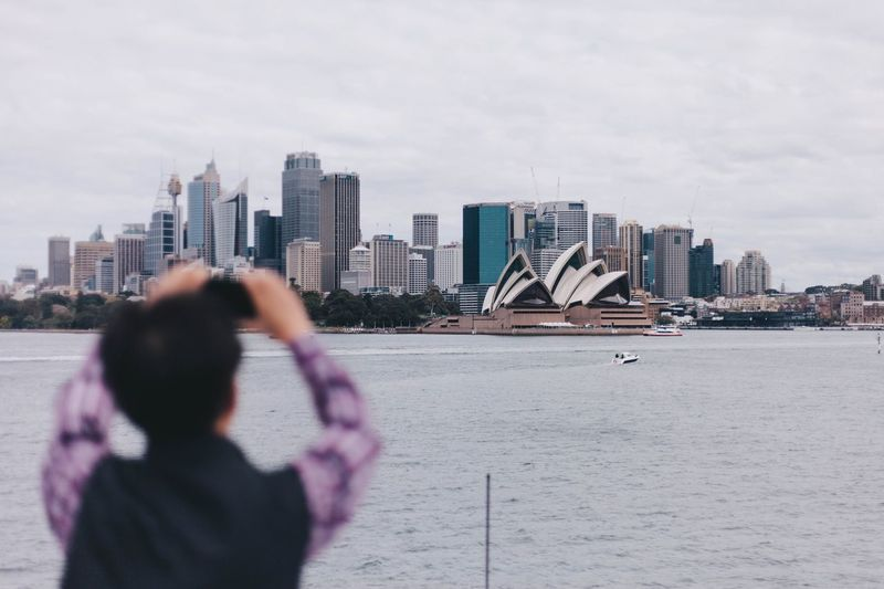Rear View Of Man Photographing Sydney Opera House And Cityscape