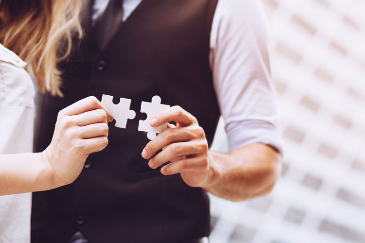 Business Adult Businessman Businesswoman Close-up Focus On Foreground Front View Hand Holding Human Hand Indoors  Leisure Activity Leisure Games Lifestyles Men Midsection People Real People Strategy Togetherness Two People Women