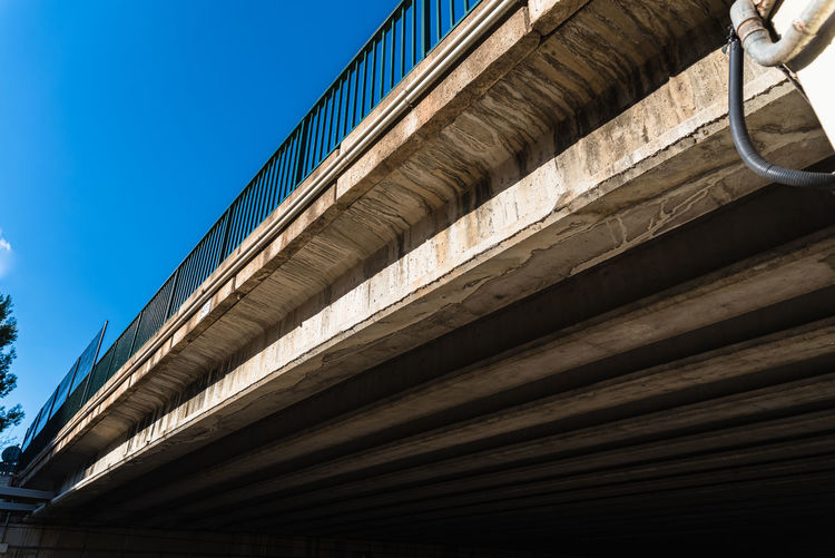Low angle view of bridge and building against clear blue sky