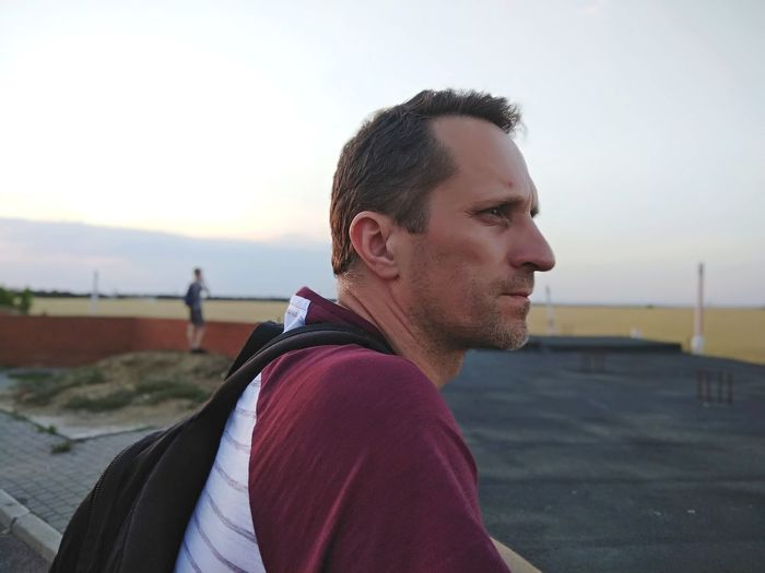 Side view of man with backpack looking away against clear sky