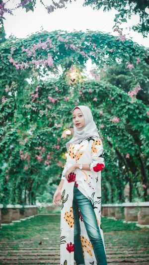 Woman standing by flowers against trees