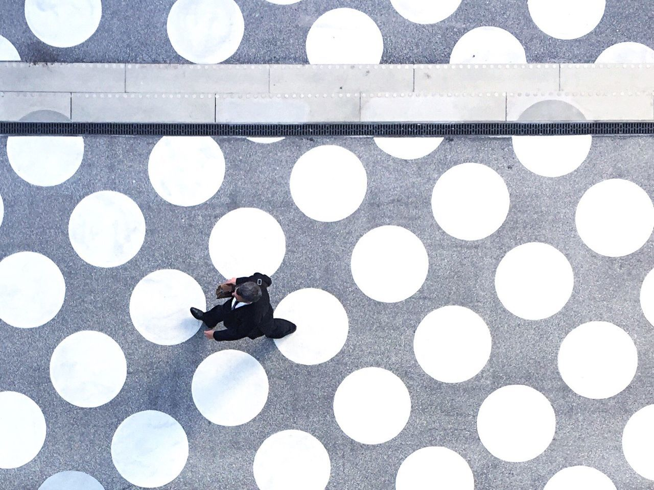 Directly Above Shot Of Businessman Walking On Patterned Footpath