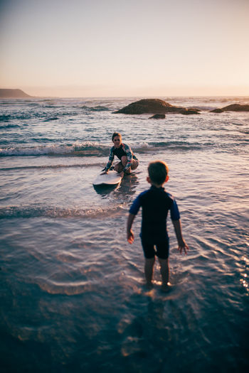 Rear view of boy standing in water while mother holding surfboard on beach