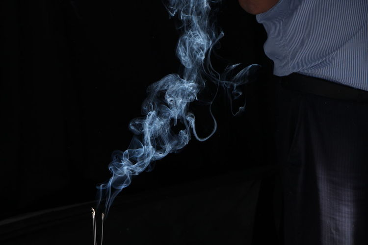 Close-up of incenses burning against black background
