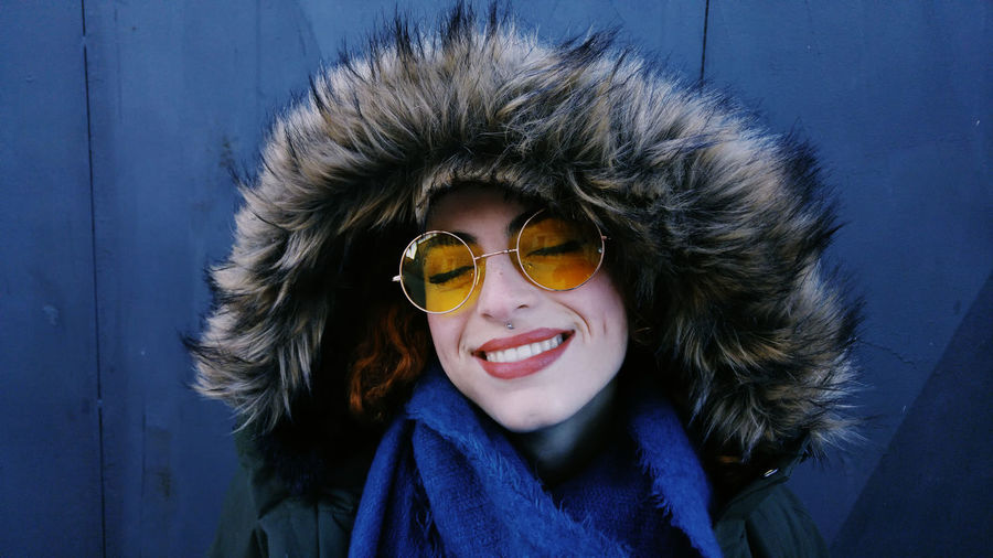 Close-Up Of Young Woman In Fur Coat And Sunglasses