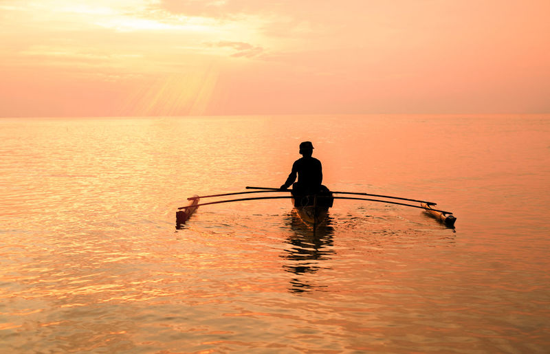 sunrise with fsherman. Water Sunset One Person Sky Silhouette Sea Nautical Vessel Nature Orange Color Beauty In Nature Transportation Scenics - Nature Lifestyles Men Waterfront Real People Sport Leisure Activity Outdoors Horizon Over Water Effort
