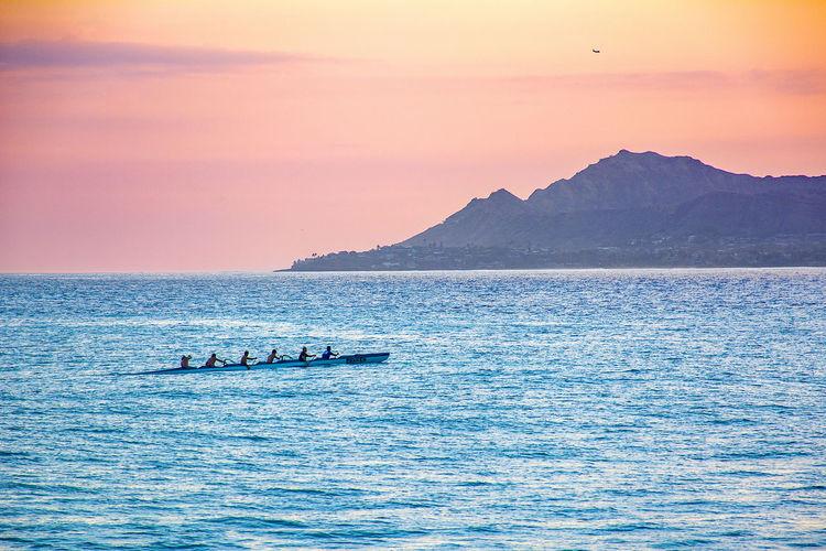 Hawaiian outrigger crew paddling at sunset